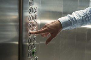 wciskanie guzika na panelu windy